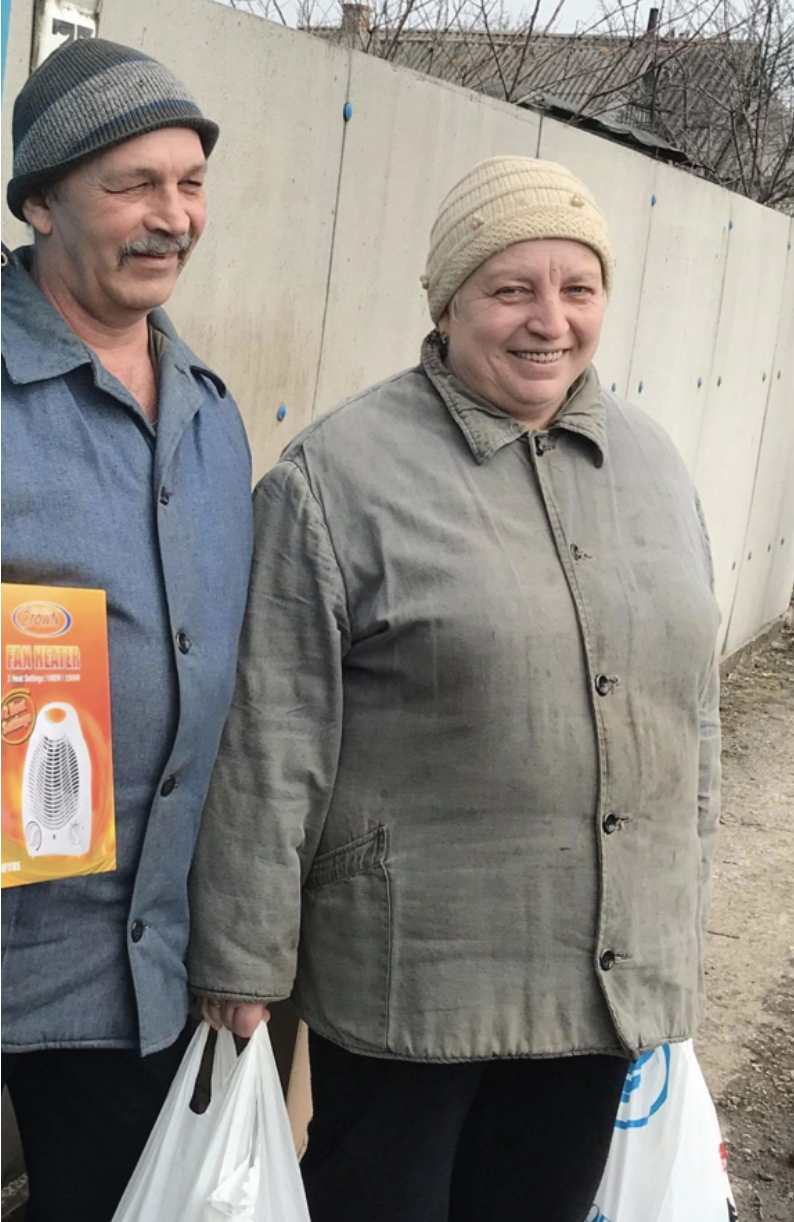 A couple is excited to receive relief packages in Avdeevka.
