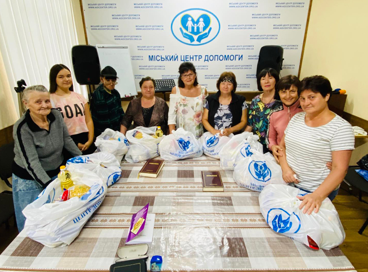 Liliya (middle, in white) and other ladies receive much-needed bags of aid.