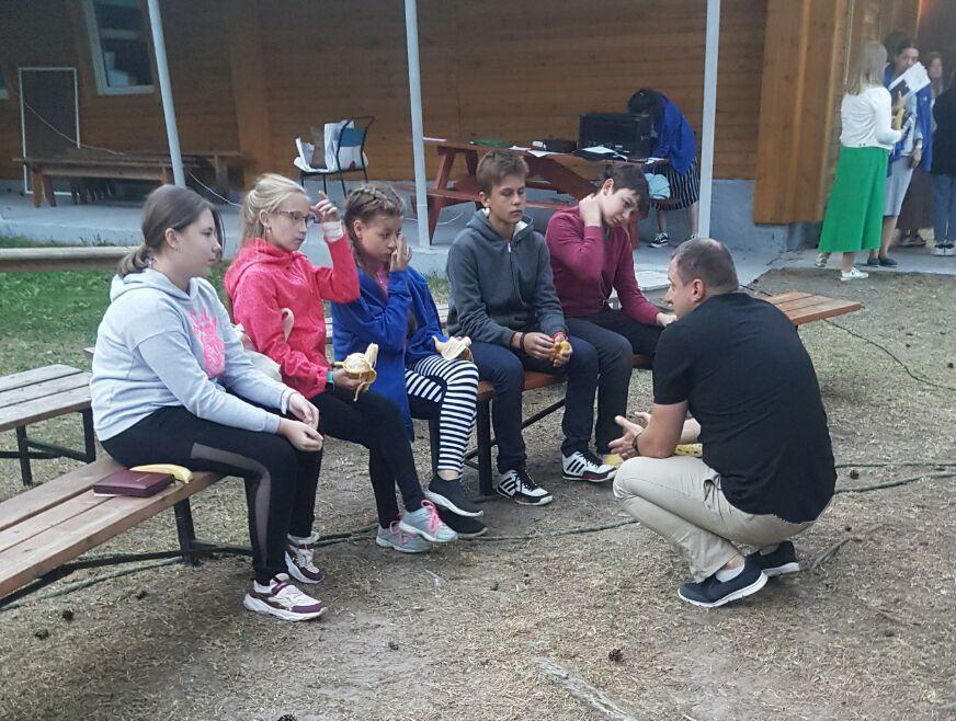 A camp leader talks with some of the children who repented and came to Christ.