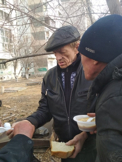 Yevgeny passes out food to men living on the street.